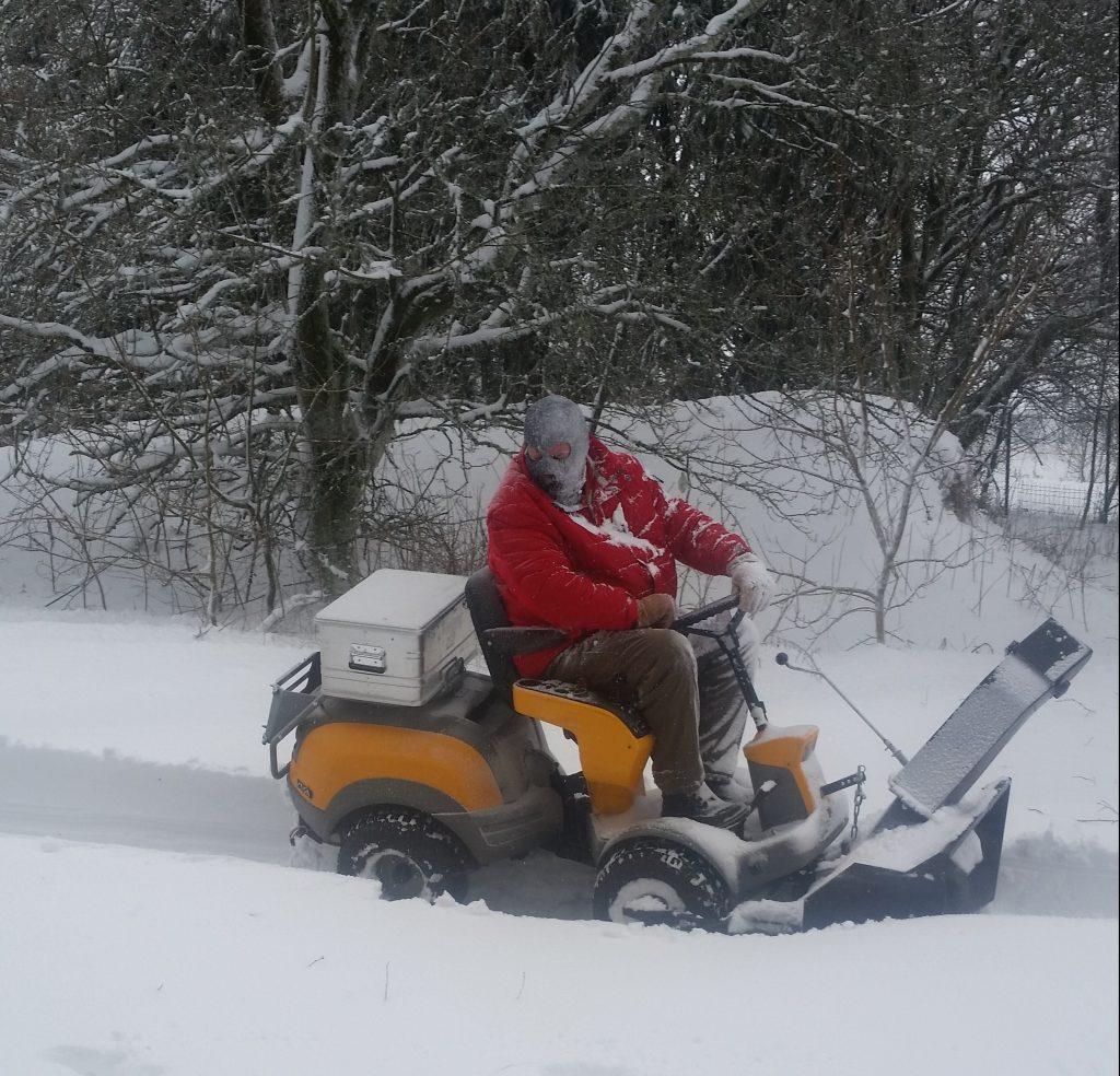 Mann auf Schneefräse sitzend